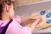 Little girl works with the dough in the kitchen — Stock Photo