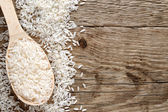 Raw white rice in spoon on wooden background — Stock Photo