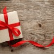 Stock Photo: Gift box with red bow on wood background