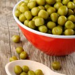Canned peas in bowl and spoon on wooden background - Stock Photo
