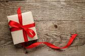 συσκευασία δώρου, με κόκκινο φιόγκο, σε φόντο ξύλου — Φωτογραφία Αρχείου