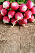 Bunch of radishes on wooden background — Stock Photo