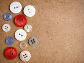 Buttons on cardboard background — Stock Photo