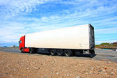 A big red and white lorry against blue sky — Stock Photo
