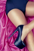 Sexy girl with high heels on satin — Stok fotoğraf