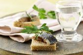 Piece of herring on rye bread on a wooden board — Stock Photo