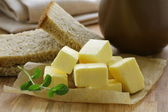 Fresh yellow butter on a wooden table — Stock Photo