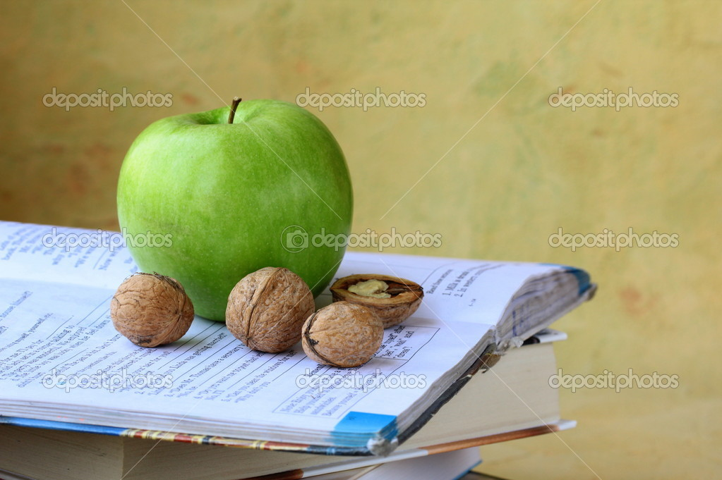 Green apple and walnuts on a pile of books — Stock Photo #10497624