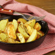 Fresh potatoes fried in a pan on a wooden table — Stock Photo