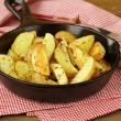 Fresh potatoes fried in a pan on a wooden table — Stock Photo #10726329