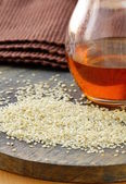 Sesame seeds and sesame oil in a bottle — Stock Photo