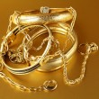 Stock Photo: Gold jewelry, bracelets and chains on gold background
