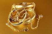 Złota biżuteria, bransoletki i łańcuchów na złotym tle — Zdjęcie stockowe