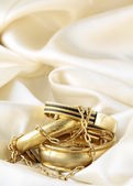 Gold jewelry, bracelets and chains on silk — Stock Photo