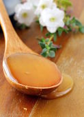 Fresh golden honey with a wooden spoon and flowers — Stock Photo