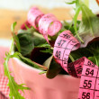 Mix salad (arugula, iceberg, red beet) with a pink measuring tape — Stock Photo