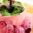 Mix salad (arugula, iceberg, red beet) with a pink measuring tape — Stock Photo #9265530