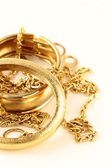 Gold jewelry, bracelets and chains on a white background — Stock Photo