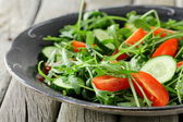 Salad with arugula and cherry tomatoes on black vintage plate — Stock Photo