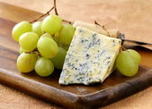 Blue cheese and white grapes on a wooden board — Stock Photo