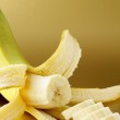Ripe banana cut into slices on a gold background — Stock Photo #9572417