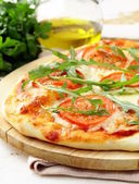 Margarita pizza with tomatoes and with arugula, on the board — Stock Photo