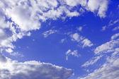 Beyaz bulutlar mavi gökyüzü çevresinde — Stok fotoğraf