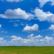 Cloudscape over green field — Stock Photo