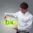Stock Photo: Businessman holding virtual eco sign