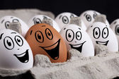 Eggs with smiley faces in eggshell — Stock Photo