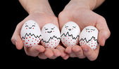 Hand holding cute eggs with funny face smileys — Foto Stock