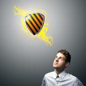 仮想の盾の記号を見ている実業家 — ストック写真