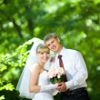 Bride and groom with a bouquet of smiles — Stock Photo