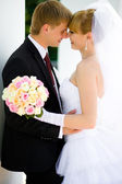 Bride and groom in the arms — Stock Photo