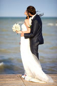 Young beautiful pair of newlyweds on the sea — Stock Photo