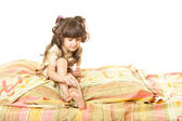 A little girl sitting on a bed — Stock Photo