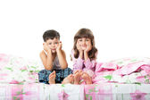 Little girl and boy sitting on the bed — Stock Photo