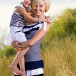 Mother and daughter playing at the river bank — Stock Photo