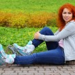 Relaxing ginger girl on skates - Stock Photo