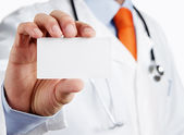 Doctor holding blank business card — Stock Photo