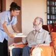Elderly senior being brought meal by carer or nurse - Stok fotoğraf