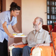 Elderly senior being brought meal by carer or nurse - Stock Photo