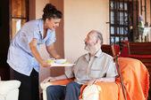 Oudere senior gebracht maaltijd door verzorgers of verpleegkundige — Stockfoto