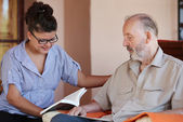 Carer reading to senior — Stok fotoğraf