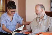 Cuidador leyendo a senior — Foto de Stock