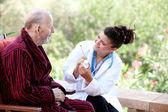 Starszy człowiek z lekarzem lub pielęgniarką — Zdjęcie stockowe