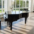 Grand piano in the hall shined by the sun - Stock Photo