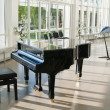 Grand piano in hall shined by sun — Stock Photo #10547429