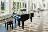 Grand piano in the hall shined by the sun — Stock Photo
