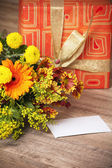 Giftbox and a bouquet of flowers — Stock Photo